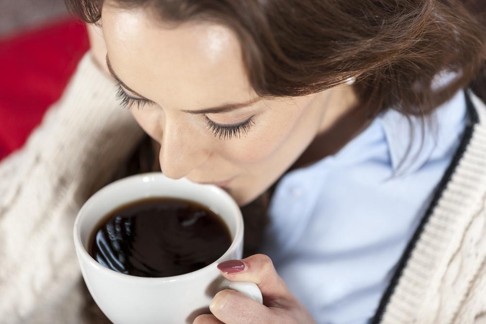 Beautiful young woman enjoying a fresh cup of coffee in a coffee shop