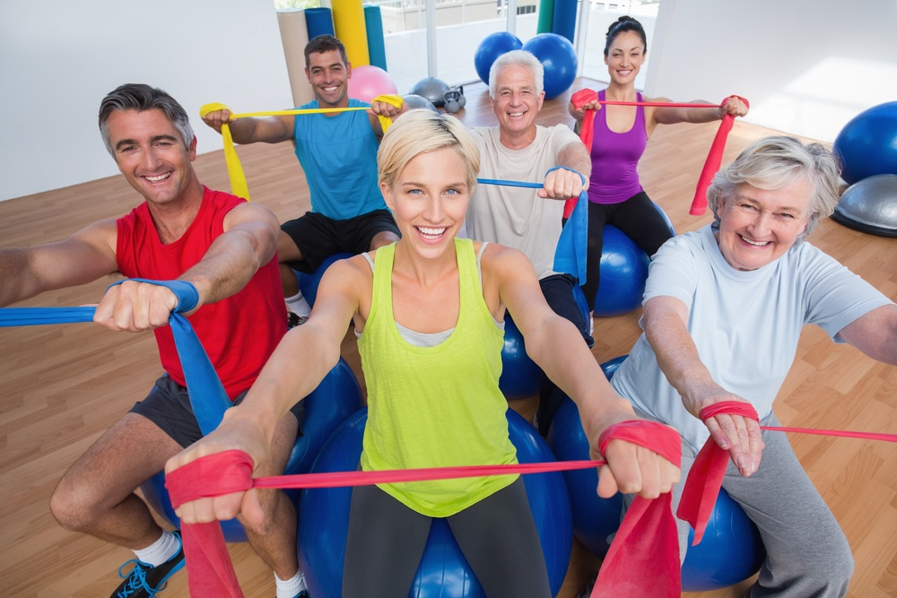 Portrait of happy men and women on fitness balls exercising with resistance bands in gym class-2