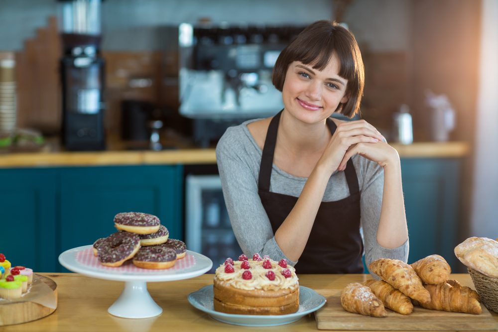Portrait of waitress sitting at counter with sweet food on table in cafx92xA9